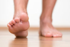 Healthy male feet stepping over home-like Stock Photography