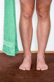 Healthy male feet with towel stepping towards. The bathroom Royalty Free Stock Image