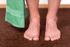 Healthy male feet with towel stepping towards. The bathroom Stock Photography