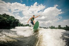 Healthy male rides the waves in a summer river. Athletic healthy male rides the waves in a summer river, having fun, spiting out spray and having nice day Stock Image