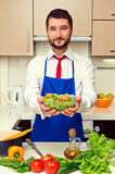 Healthy man in blue apron holding salad Stock Image