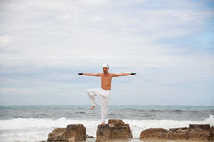Healthy man doing pilates yoga meditation on beach summer Stock Images