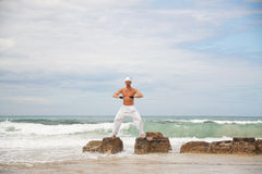 Healthy man doing pilates yoga meditation on beach summer Royalty Free Stock Image