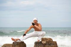 Healthy man doing pilates yoga meditation on beach summer Stock Photo