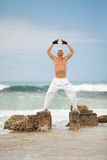 Healthy man doing pilates yoga meditation on beach summer Royalty Free Stock Photos