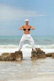 Healthy man doing pilates yoga meditation on beach summer Royalty Free Stock Photography