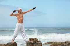 Healthy man doing pilates yoga meditation on beach summer Stock Photos