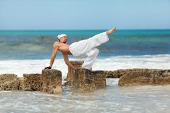 Healthy man doing pilates yoga meditation on beach summer Stock Images