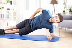 Healthy Man Doing Side Plank Exercise on a Mat. Healthy Gorgeous Man Doing an Indoor Side Plank Exercise on a Mat While Looking at the Camera stock photo
