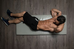 Healthy Man Doing Sit-Ups On Foor. Healthy Man Exercising Abdominals On Foor stock photo