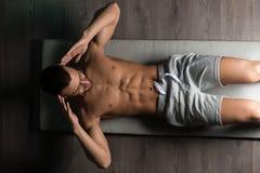 Healthy Man Doing Sit-Ups On Foor. Healthy Man Exercising Abdominals On Foor stock photos