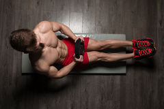 Healthy Man Doing Sit-Ups On Foor With Weights. Healthy Young Man Exercising Abdominals On Foor With Weights stock images