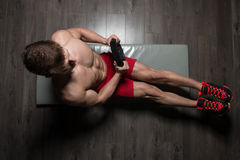 Healthy Man Doing Sit-Ups On Foor With Weights. Healthy Young Man Exercising Abdominals On Foor With Weights royalty free stock photography