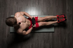 Healthy Man Doing Sit-Ups On Foor With Weights. Healthy Young Man Exercising Abdominals On Foor With Weights royalty free stock images