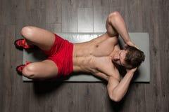 Healthy Man Doing Sit-Ups On Foor. Young Healthy Man Exercising Abdominals On Foor stock photos