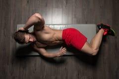 Healthy Man Doing Sit-Ups On Foor. Young Healthy Man Exercising Abdominals On Foor stock image