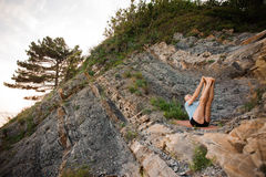 Healthy man doing yoga sitting back on rocks stock photography