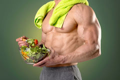 Healthy man eating a salad. Powerful athletic man with great body eating a healthy salad Royalty Free Stock Photo