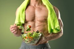 Healthy man eating a salad. Powerful athletic man with great phisique eating a healthy salad Stock Images