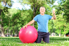Healthy man giving thumb up seated on exercise mat outdoors Stock Photo