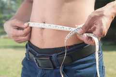 Healthy man measuring his body. Cropped and mid-section image of. Young man measuring his waist with tape measure against out door background. Health and Stock Images