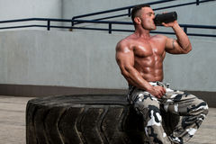 Healthy man resting and drinking water after exercising in gym Stock Photography