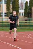 Healthy man run on athletics race sport track and representing c. Oncept of sport and speed Stock Photo