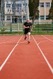 Healthy man run on athletics race sport track and representing c. Oncept of sport and speed Stock Image