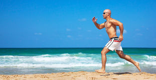 Healthy man running on the beach. Doing sport outdoor, freedom, vacation, heath care concept with copy space over natural background Royalty Free Stock Images