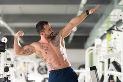 Healthy Man Showing Abdominal Muscle. Healthy Young Tattoo Man Standing Strong In The Gym And Flexing Muscles - Muscular Athletic Bodybuilder Fitness Model stock images