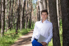 Healthy man standing in the forest and in the hands holding a laptop Stock Photo