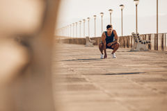 Healthy man taking a break after morning run. Shot of healthy young man taking a break after morning run. Male runner resting after running on promenade Royalty Free Stock Image
