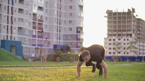 Healthy man training back flip exercise intense muscle workout muscular bodybuilder doing superman enjoying extreme. Fitness routine in city park slow motion stock video