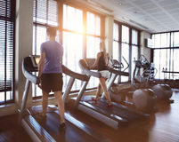 Healthy man and woman running on a treadmill in a gym. Stock Photos