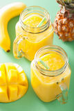 Healthy mango pineapple smoothie in mason jars.  Stock Image