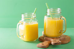 Healthy mango pineapple smoothie in mason jars Stock Photography