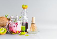 Healthy matcha fusion green tea vegan latte in glass jar with ingredients on table. Matcha espresso drink with pink fruits juice. Antioxidants, detox and stock image