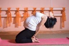 Pregnant. Healthy maternity lifestyle concept. 40 week pregnant middle aged caucasian woman doing yoga exercises ardha kamalamunyasana royalty free stock photos