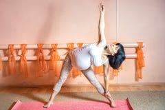 Pregnant. Healthy maternity lifestyle concept. 40 week pregnant middle aged caucasian woman doing yoga exercises Utthita Trikonasana or triangle pose stock photo