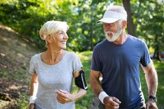 Healthy mature couple jogging in a park at early morning with sunrise royalty free stock image