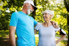 Healthy mature couple jogging in a park at early morning with sunrise stock photography