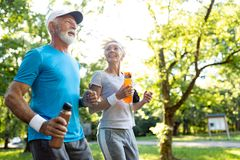 Healthy mature couple jogging in a park at early morning with sunrise royalty free stock images