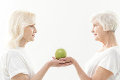 Healthy mature ladies prefer healthy eating. Friendly old women are standing and holding apple in their hands. They are looking at each other with care and stock photography