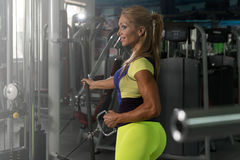 Healthy Mature Woman Doing Back On Cable Machine Stock Photography