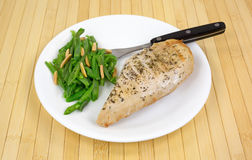 Healthy meal of chicken and green beans. A cooked chicken breast with green beans and sliced almonds on a white plate with fork atop a wood placemat royalty free stock image
