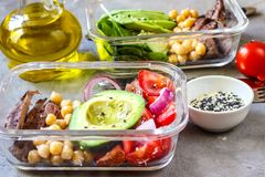 Healthy meal prep containers with chickpeas, goose meat. Tomatoes, avocado, lemon and spinach. Top view stock photos