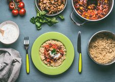 Healthy meal with quinoa, tomatoes beans sauce and fried chicken meat on kitchen table background. With food pots bowls and cutlery , top view stock image