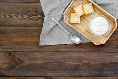 Healthy meal. White mushroom cream soup served with rusks on dark wooden background top view copy space. Healthy meal. White mushroom cream soup served with Stock Photo