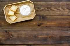 Healthy meal. White mushroom cream soup served with rusks on dark wooden background top view copy space. Healthy meal. White mushroom cream soup served with Stock Images