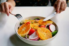 Healthy meals, diet recipes, A hand are using fork and knife to eat of mixed salad with preserved salmon on white plate and white. Healthy meals, diet recipes, A Stock Photo